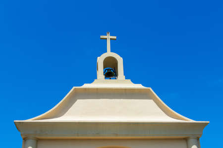 Exterior view of a top of small Catholic church with bell tower, one bell and cross under birght blue sky.