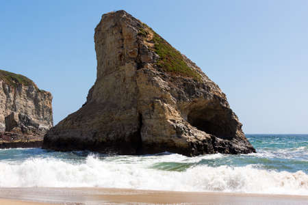 Rocky outcrop surrounded by waves at Shark Fin Cove beach on Pacific Ocean coast of California.