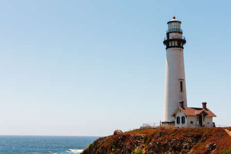Abandoned and weathered lighthouse stands on California Pacific Ocean coast under blue sky at the daytime