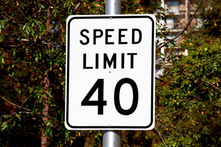 Forty mph speed limit sign on urban road. Speed zone traffic sign against tree landscape. Foto de archivo