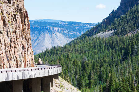Scenic view of Chittenden viaduct on Grand Loop Road. Golden Gate Canyon surrounded by steep and colorful rocky walls in Yellowstone National Park.