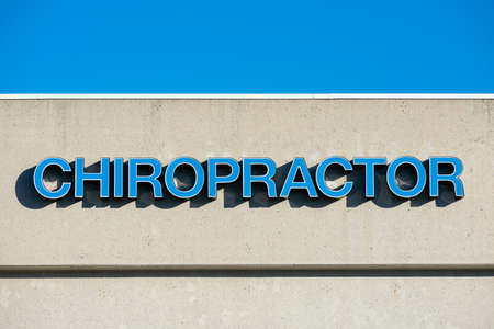 Chiropractor sign in blue letters on commercial building exterior.