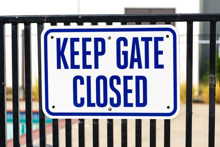 Keep Gate Closed warning sign on the entrance door to outdoor pool to remind people to keep the swimming pool gate closed at all times. Foto de archivo