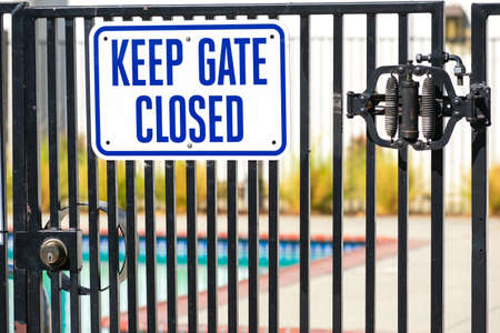 Keep Gate Closed warning sign on the locked entrance door to outdoor pool to remind people to keep the swimming pool gate closed. Foto de archivo