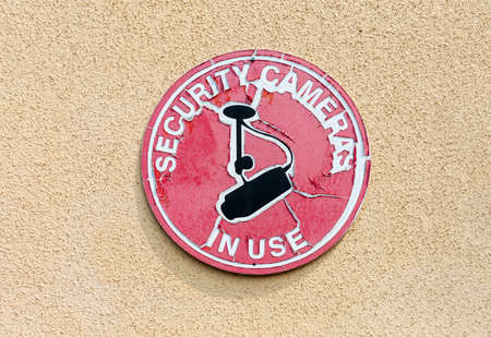 Weathered security cameras in use outdoor red circle sign on the beige building wall.