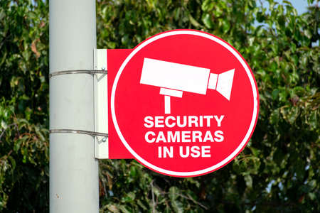 Security cameras in use outdoor red circle sign attached to the pole. Blurred trees background.
