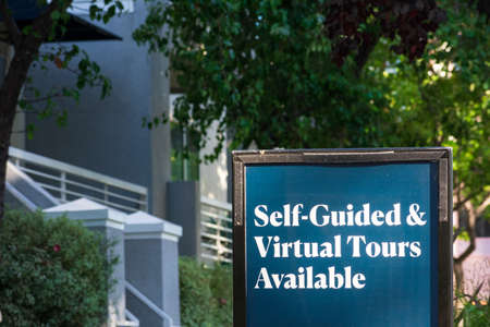 Self-Guided and Virtual Tours Available sign near an apartment building.