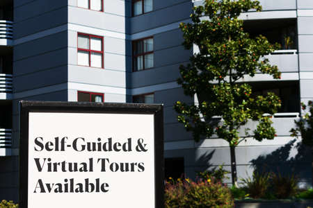 Self-Guided and Virtual Tours Available sign near a luxury apartment building. Foto de archivo