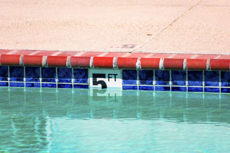 Swimming pool depth marker identifies the water depth for swimmers. Five feet depth sign.