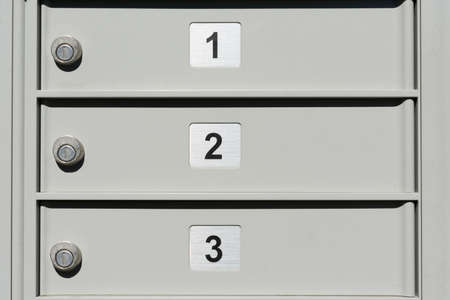Close up. Locked doors of outdoor apartment mailbox with numbers 1, 2 and 3.