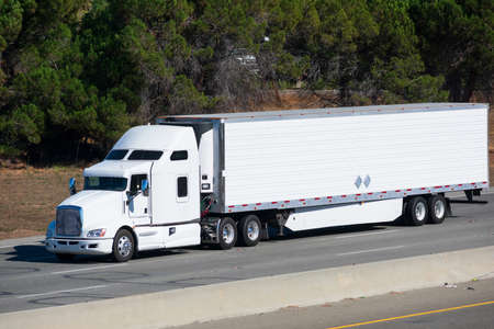 White big rig long haul semi truck transporting commercial cargo in refrigerator semi truck running on the eight lanes highway Foto de archivo