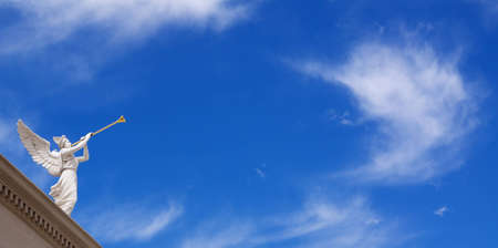 heavenly angel: Angel with horn on blue sky background with white clouds Stock Photo