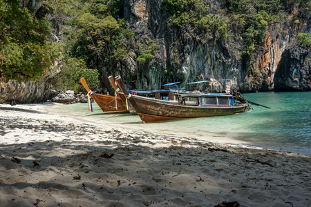 Two long tail boats on a small hidden beach in the area of Krabi, Thailand