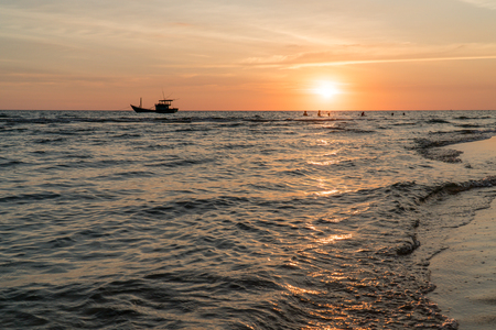 Next to a fisher boat, people are playing at sunset, Phu Quoc, Vietnam