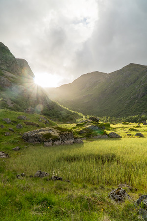 Sunrays are overlooking some mountains in the fjords of Lofoten, Norway