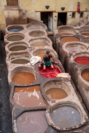A man is working at the tanneries in Fes, Morocco