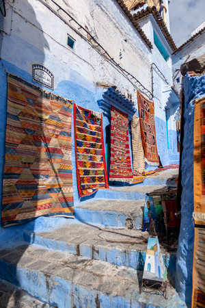 A vendor is selling some rugs in the streets of Chefchaouen, Morocco Standard-Bild