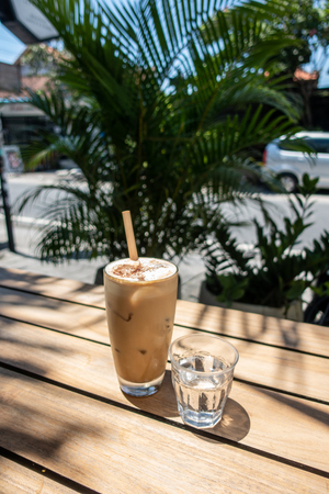 A refreshing icecold coffee with water on a wooden table in front of a green plant Stok Fotoğraf