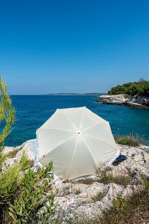 A beach umbrella on the stone coastline of Istria in Croatia