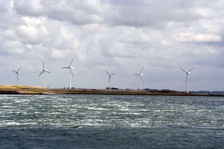 windy energy: Six windmills on the seaside shore Stock Photo