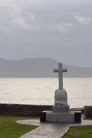 A celtic cross in front of a Irish scenery