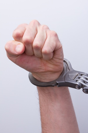 A man in metal handcuffs on a grey background Stock Photo - 13145136