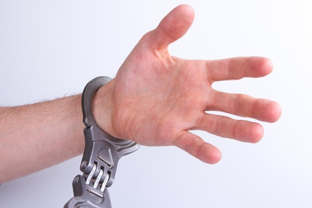 A man in metal handcuffs on a grey background photo