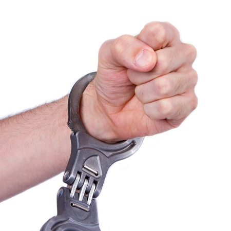 closed fist sign: A man in metal handcuffs on a white background