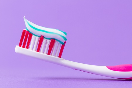 A pink toothbrush with toothpaste on a purple background