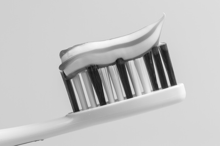 A toothbrush with toothpaste in black and white photo