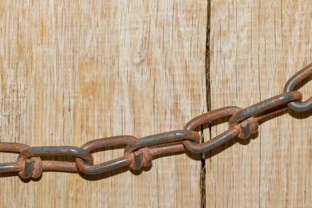 A close-up of a chain on a cracked wooden background Stock Photo - 13552763
