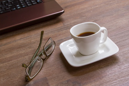 Espresso coffee with glasses on wood floor with laptop photo