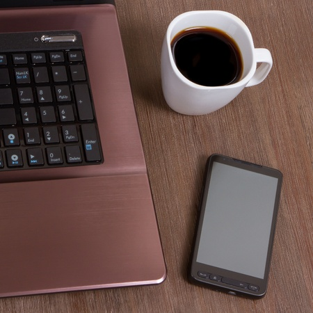 Coffee on wood floor with a laptop and a smartphone photo