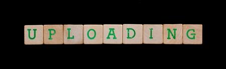 uploading: Green letters on old wooden blocks (uploading) Stock Photo