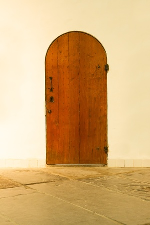 Old wooden door in a white wall Stock Photo - 13661315