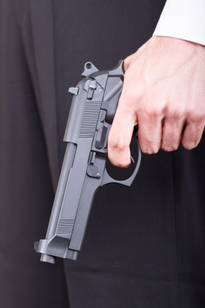 Man with gun, business suit, focus on the gun photo