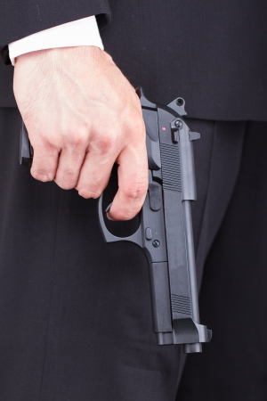 Man with gun, business suit, focus on the gun Stock Photo - 13661314