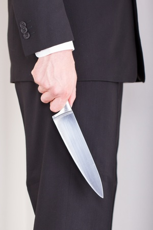 Man with knife, business suit, focus on the knife photo