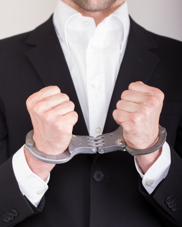 Man with handcuffs, business suit, focus on the knife photo