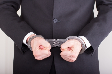 Man with handcuffs, business suit, focus on the handcuffs photo