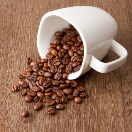 Coffee cup and spilled coffee beans on wood photo