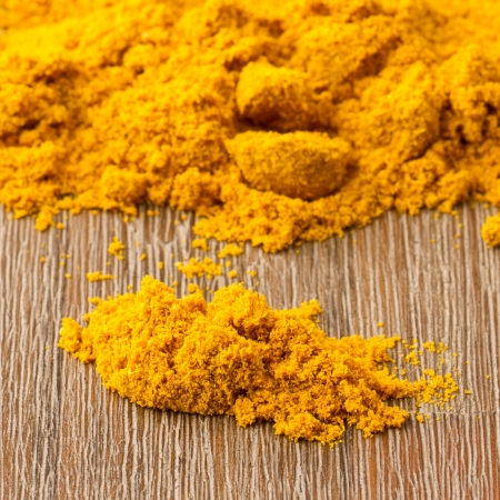Heap of turmeric on isolated wood background Stock Photo