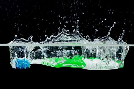 Brosse à dents avec les projections d'eau sur un fond noir Banque d'images