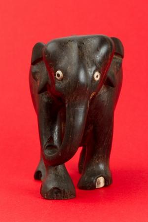 Statue d'ivoire très ancien d'un éléphant isolé sur un beckground rouge