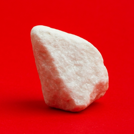 strontium: Glittering white stone isolated on a red background