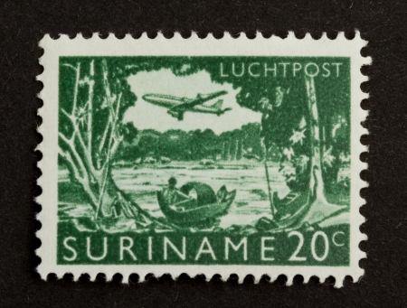 gulden: SURINAME - CIRCA 1970: Stamp printed in Suriname shows a river, boat and airplane, circa 1970 Editorial