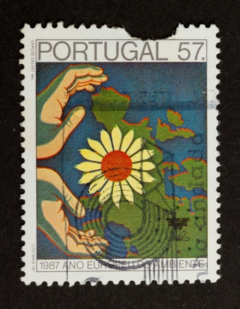 PORTUGAL - 1987: Stamp printed in Portugal shows a map of europe with a flower an hands, 1987 photo