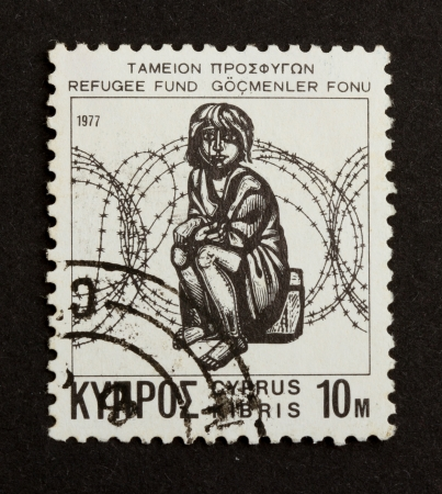 CYPRUS - 1972: Stamp printed in Cyprus shows a sitting refugee (refugee fund), 1970 photo