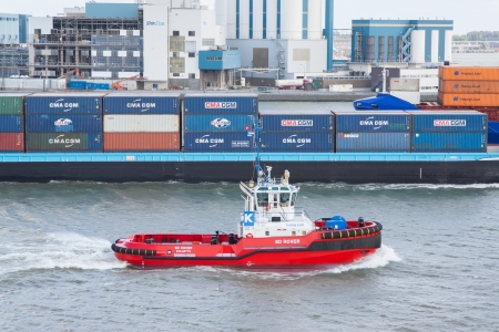 ROTTERDAM, THE NETHERLANDS - JUNE 22: Red tug is working in the harbor of Rotterdam (Holland), Rotterdam, June 22, 2012