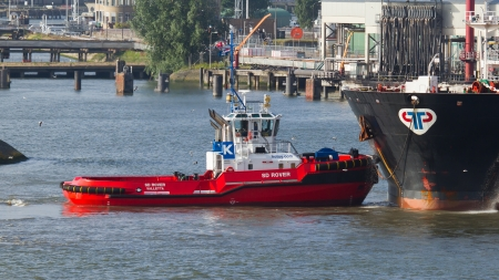 ROTTERDAM, THE NETHERLANDS - JUNE 22: Two tugboats manoeuvring an oil tanker in the dutch harbor of Rotterdam, Rotterdam, June 22, 2012